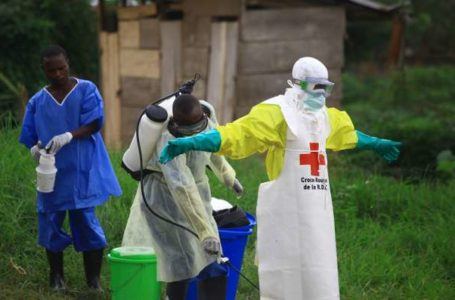 FILE – In this Sunday, Sept 9, 2018 file photo, a health worker sprays disinfectant on his colleague after working at an Ebola treatment centre in Beni, Eastern Congo. The World Health Organization is announcing on Wednesday, Oct. 17 whether Congo's latest outbreak of the deadly Ebola virus should be declared a global health emergency. (AP Photo/Al-hadji Kudra Maliro, file)