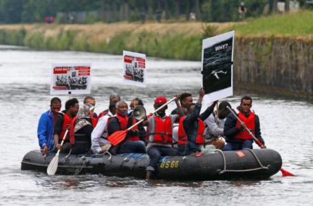 Des migrants et des militants naviguent sur un bateau pneumatique dans une action symbolique sur l'Ill près du Parlement européen à Strasbourg, en France, pour souligner la crise de l'immigration en Méditerranée