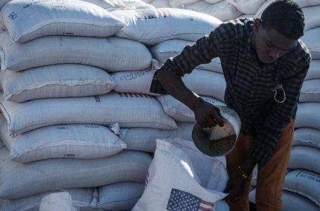 Un homme partageant de la nourriture apportée par l'USAID près de la frontière éthiopienne à Gedaref, dans l'est du Soudan, le 2 décembre 2020   –   Copyright © africanews YASUYOSHI CHIBA/AFP or licensors